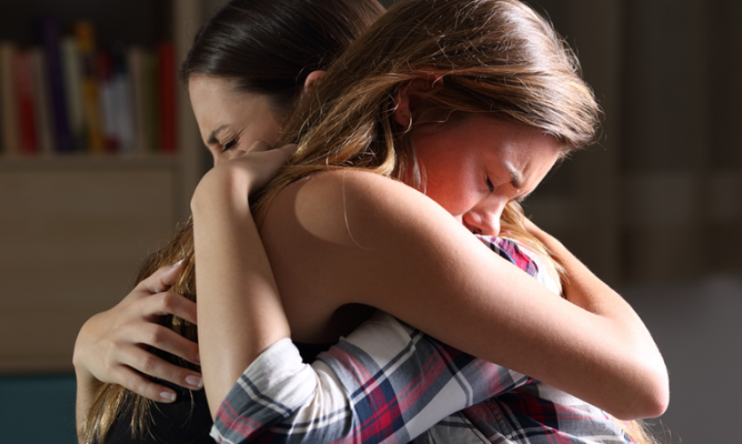 A child and their parent tightly embracing and looking distraught.