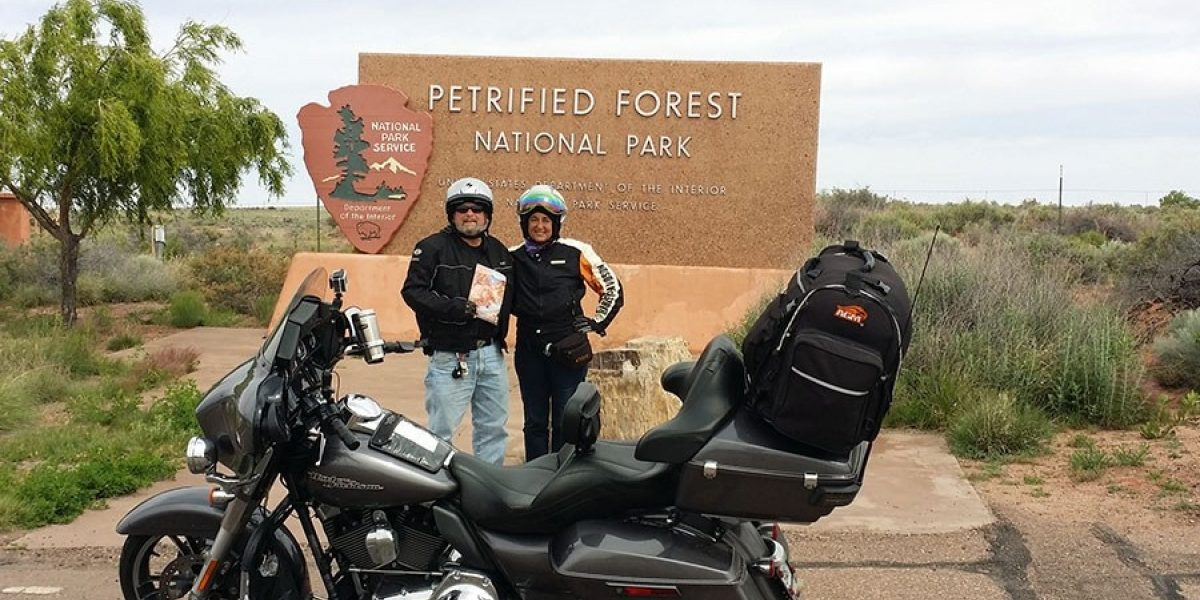 Photo of Bruce and Ellen in front of the sigh for Petrified Forest National Park on 2015 Ride for Recovery.