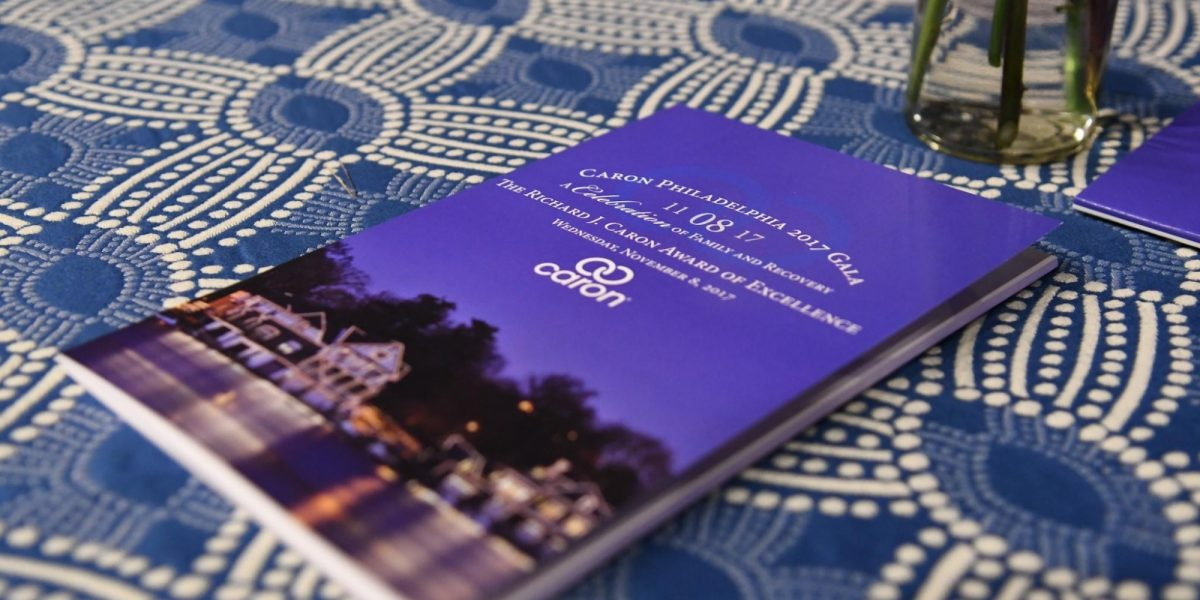 A Caron brochure laying on a blue, patterned table cloth.