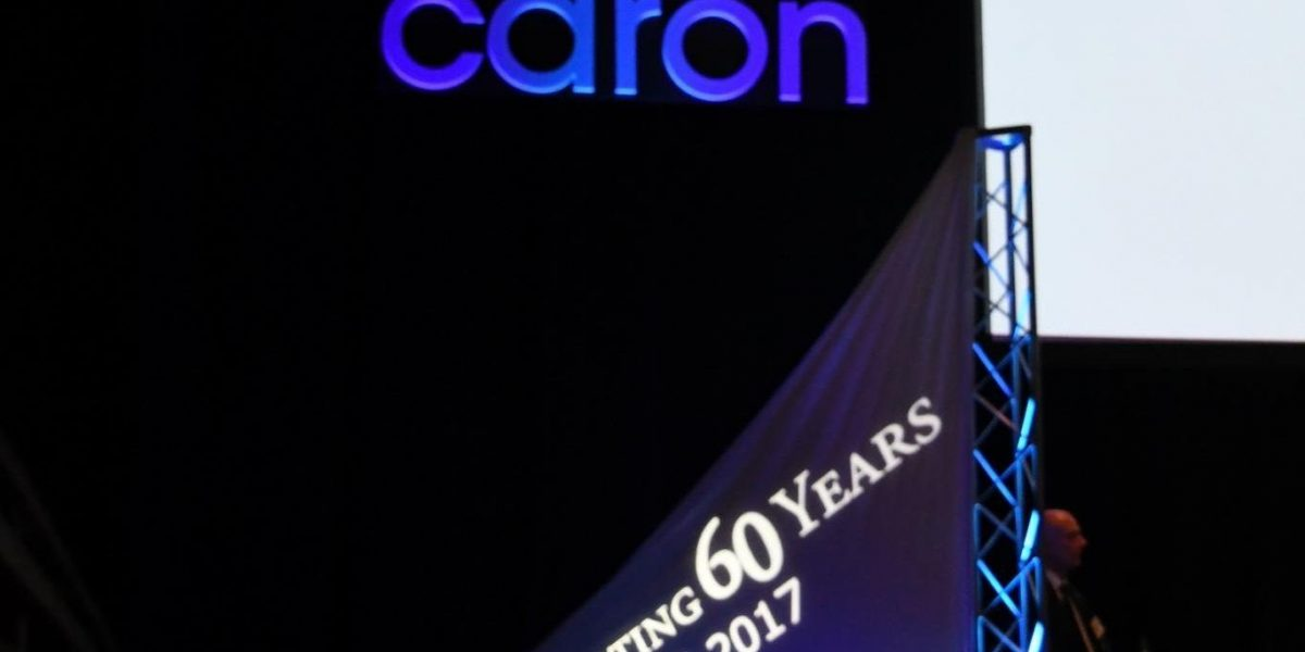 """A dark room with a glowing Caron logo on the wall above a banner that says, """"Celebrating 60 Years, 1957-2017."""""""