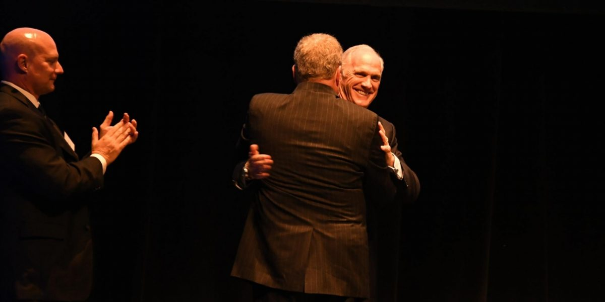 The people standing on a stage in front of a dark curtain. Two of the people are hugging each other.