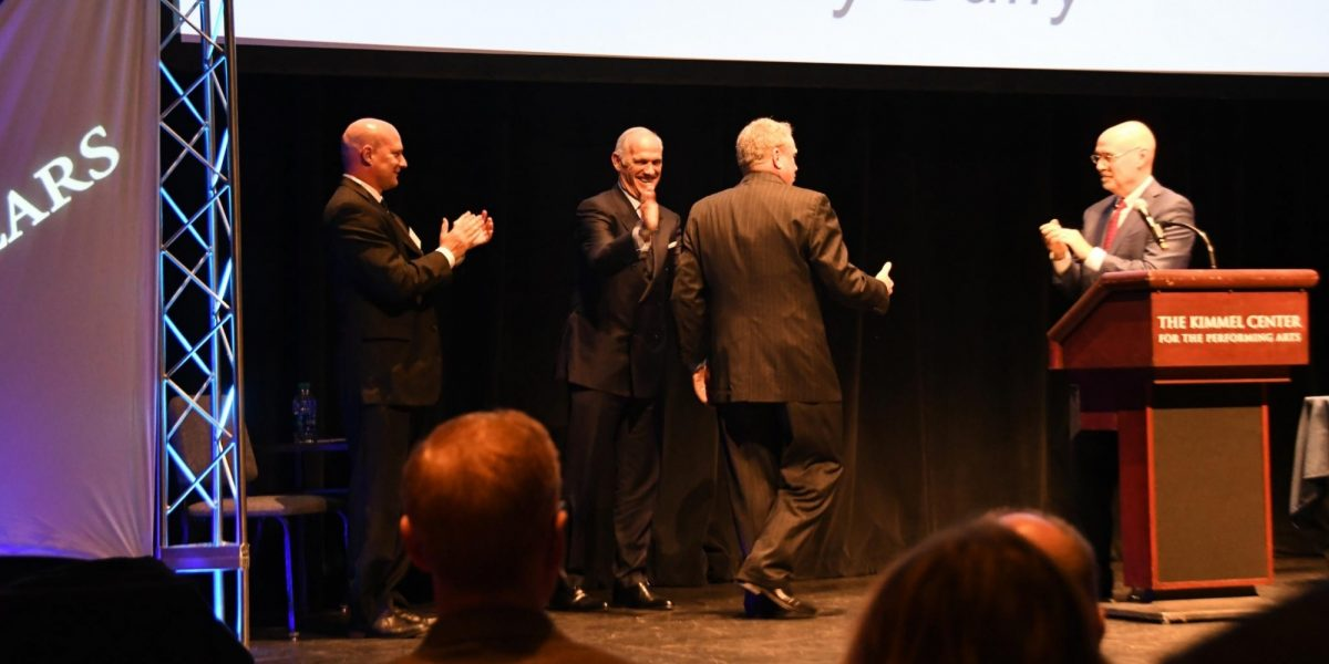 Four men in dark suits standing on stage. Three of the men are clapping, while the fourth man is approaching a podium to receive an award.