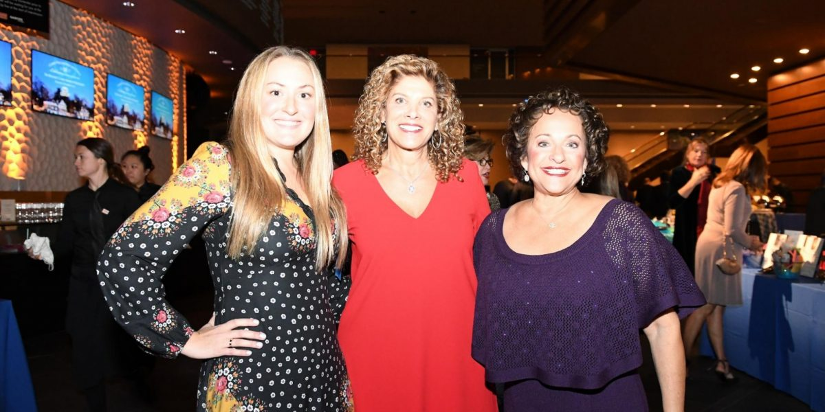Three gala attendees standing with their arms around each other.