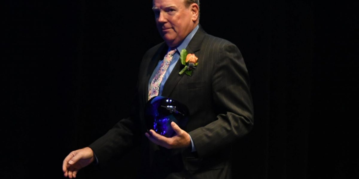 A man a dark suit, holding an award in one hand.