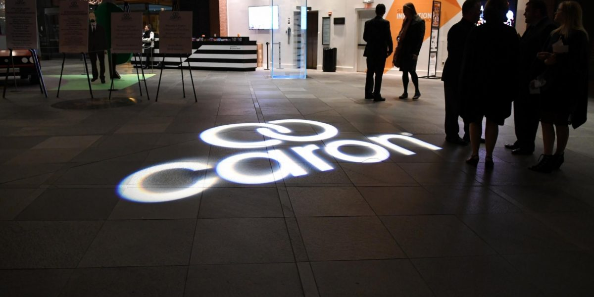A dark room with the Caron logo projected on the ground.