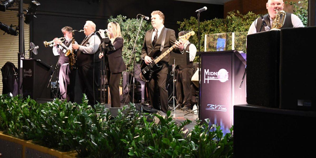 A musical group standing on a stage that is decorated with greenery.