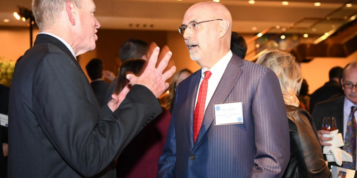 Two gala attendees facing each other and having a conversation. The person on the left is using their hands to express themselves in conversation.