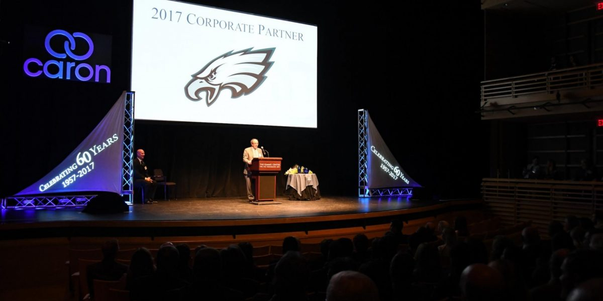 A person standing behind a podium on a stage, in front of a large screen displaying the Philadelphia Eagles NFL logo.