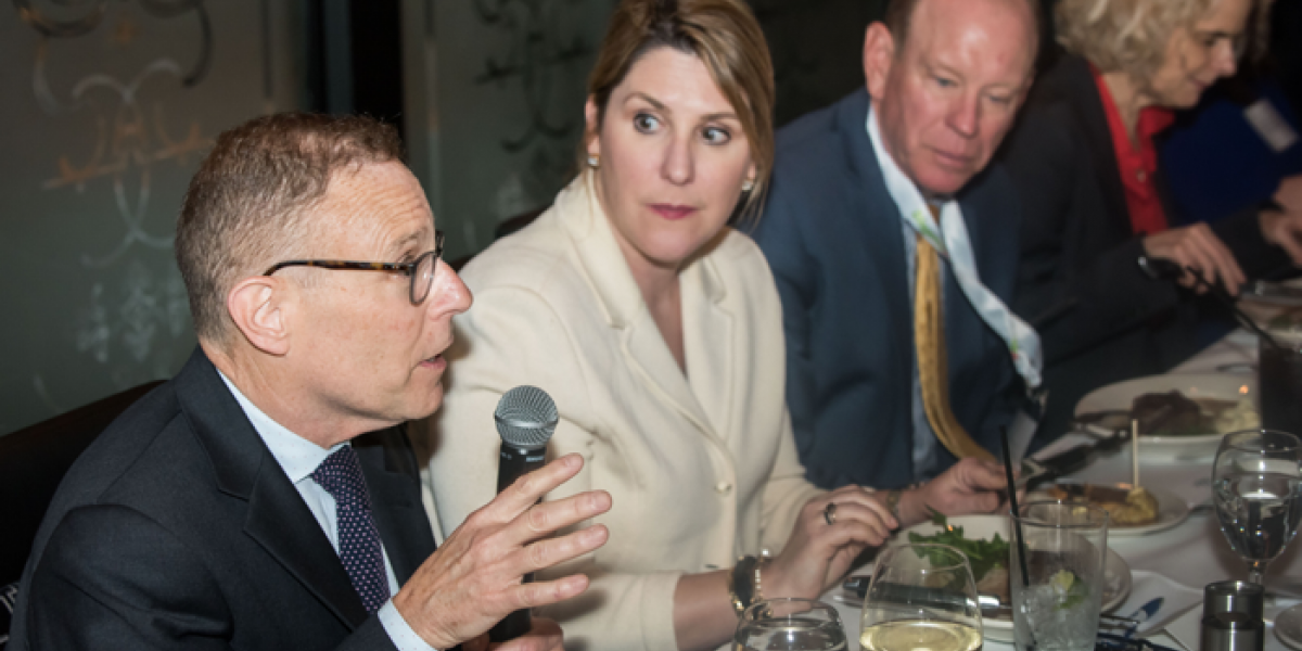 Group of experts at a table, one man speaking into a microphone.