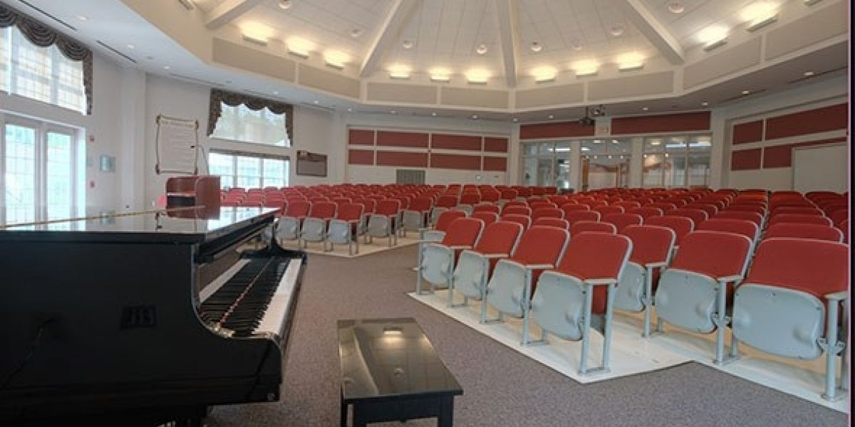 Photo of the auditorium taken from the front or stage area, with a grand piano nearby.