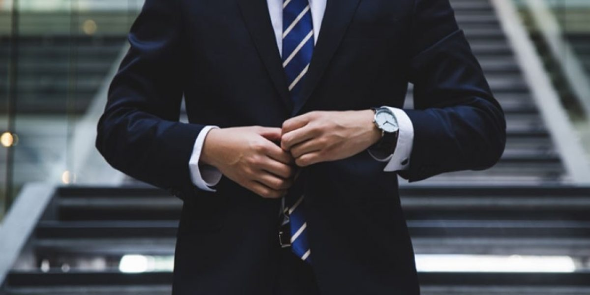 Person wearing a suit and tie, fastening the jacket closed.