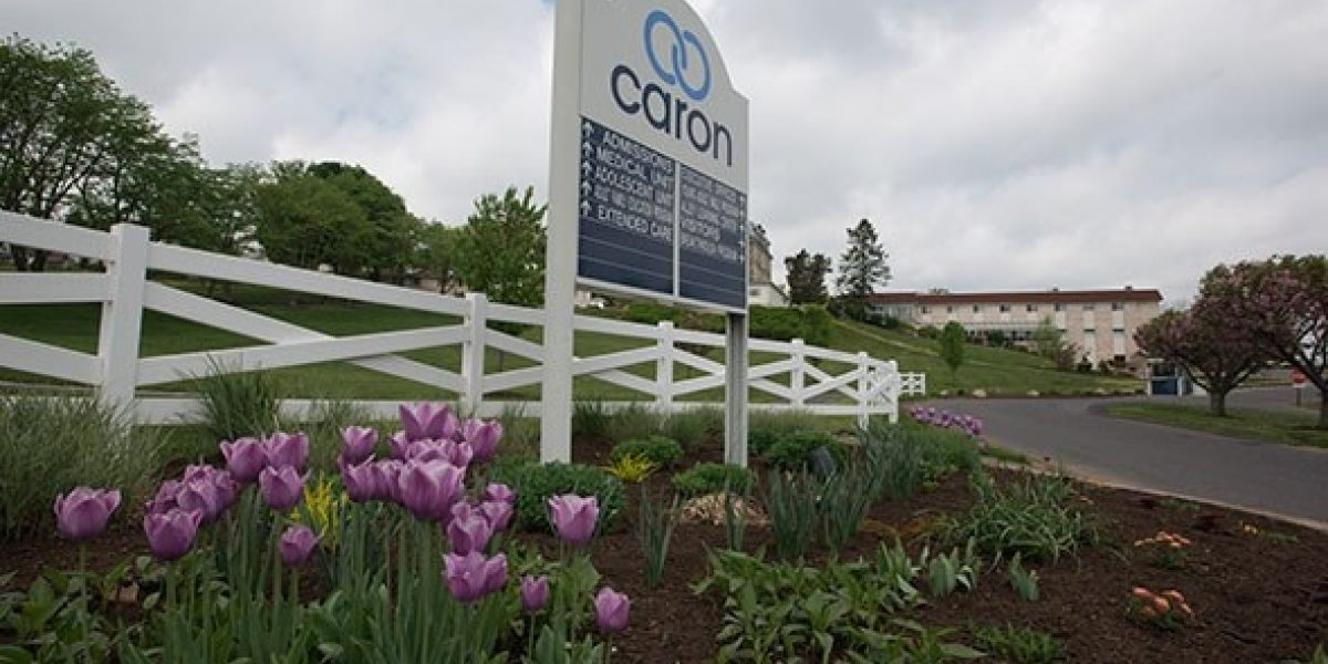 Photo of the main entrance to the treatment center with a large white Caron sign and tulips underneath it.
