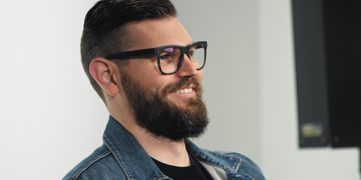 A photo of a man with glasses and beard, sitting in front of a camera smiling.