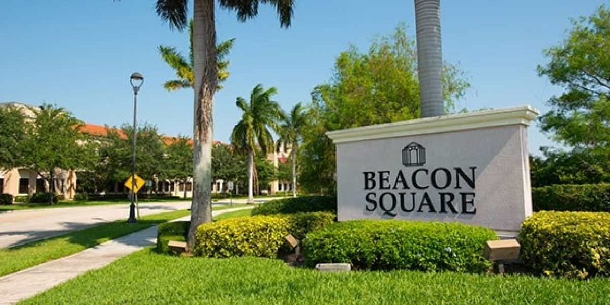 Photo of Beacon Square's front drive, with blue skies and palm trees out front and paved sidewalks nearby.