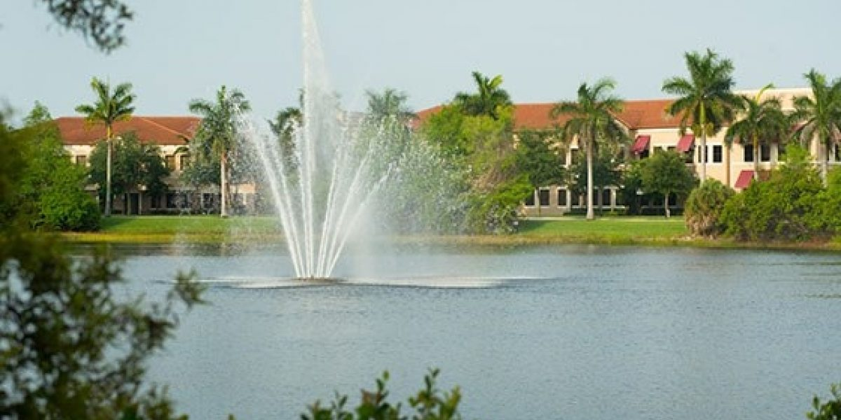 Photo of a resplendent fountain sprays water from the center of a pond on Renaissance's campus.