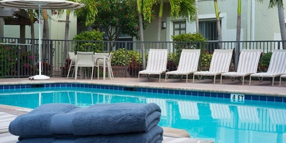 Photo of the outdoor pool at the Renaissance residences, with towels and lounge chairs near the pool.