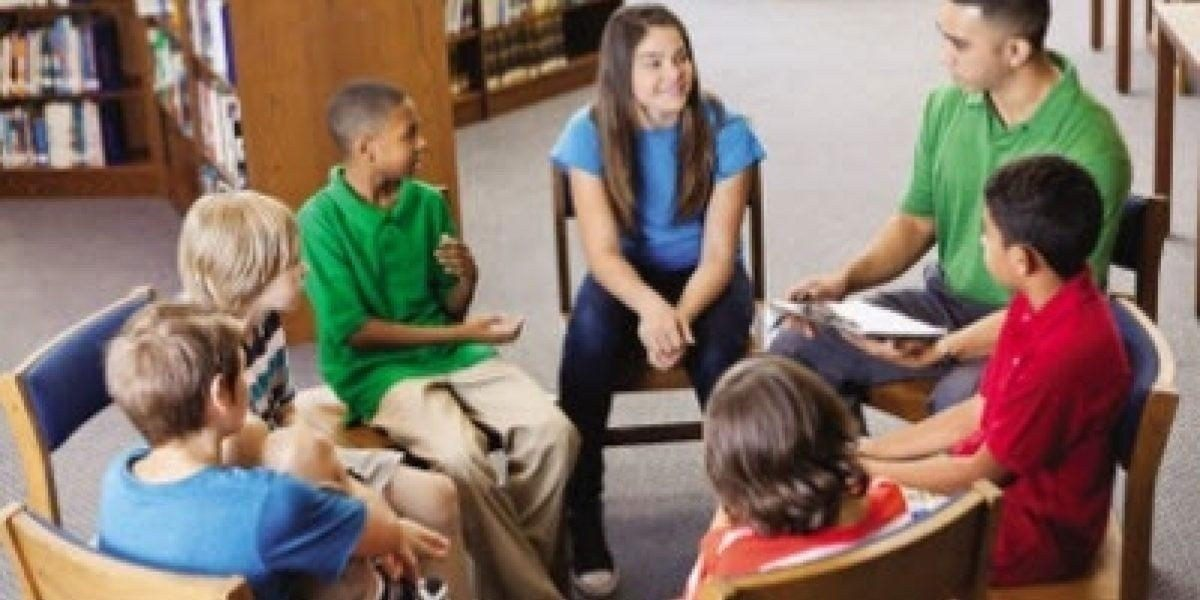 A group of teens sitting in a circle in the library talking.