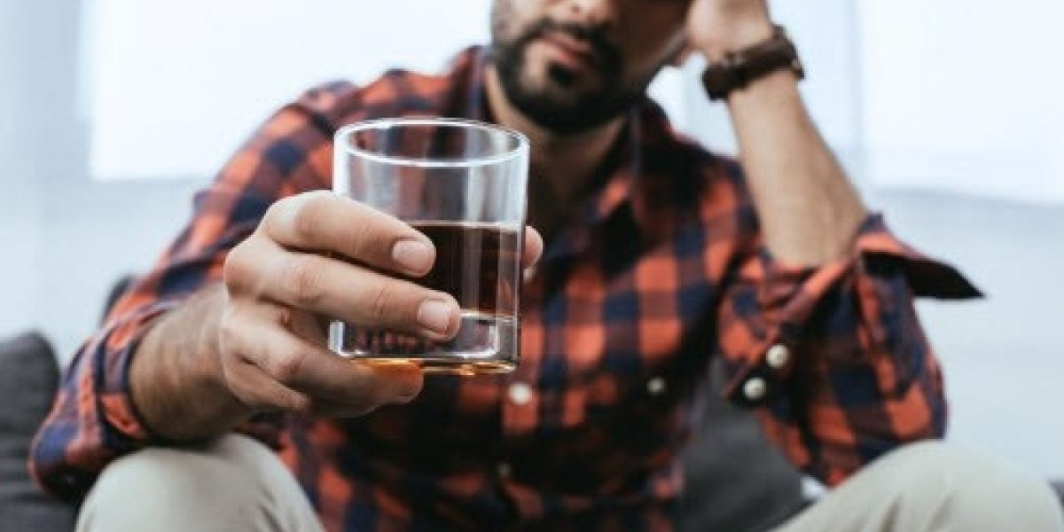 Person sitting, looking distraught, holding a glass of brown liquor.