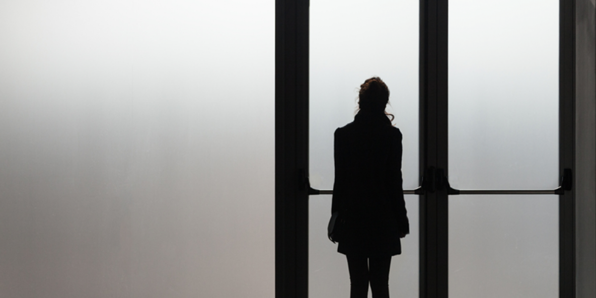 Silhouette in black of a teen in front of a misty glass door.