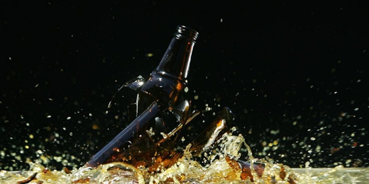Broken beer bottle shattering on the floor.