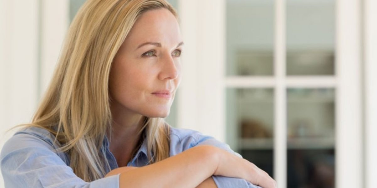 Woman with arms crossed looks thoughtfully into the distance.
