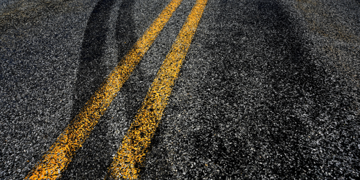 Close up of asphalt with tire tracks crossing the lane dividing lines.