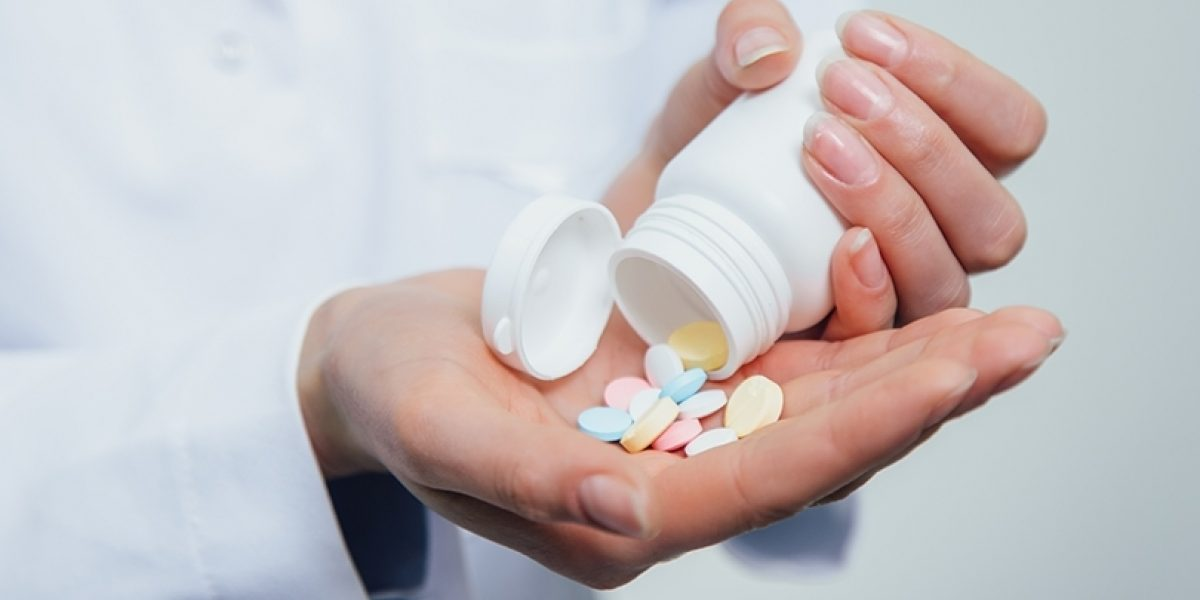 Hands dumping pills out of a pill bottle.