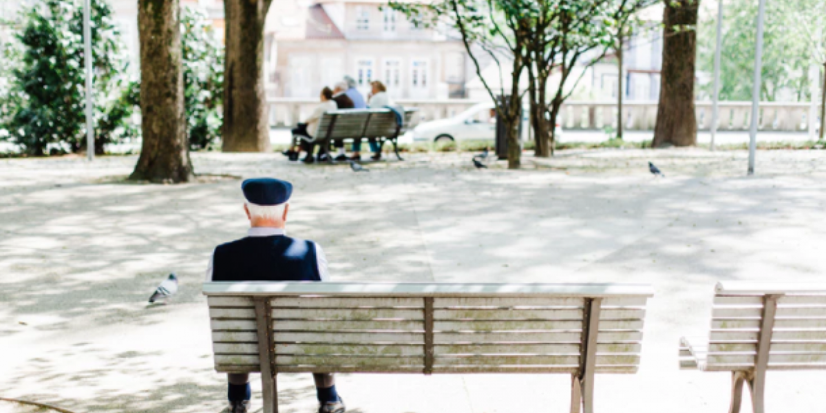 View from behind a park bench where an older man sits alone.