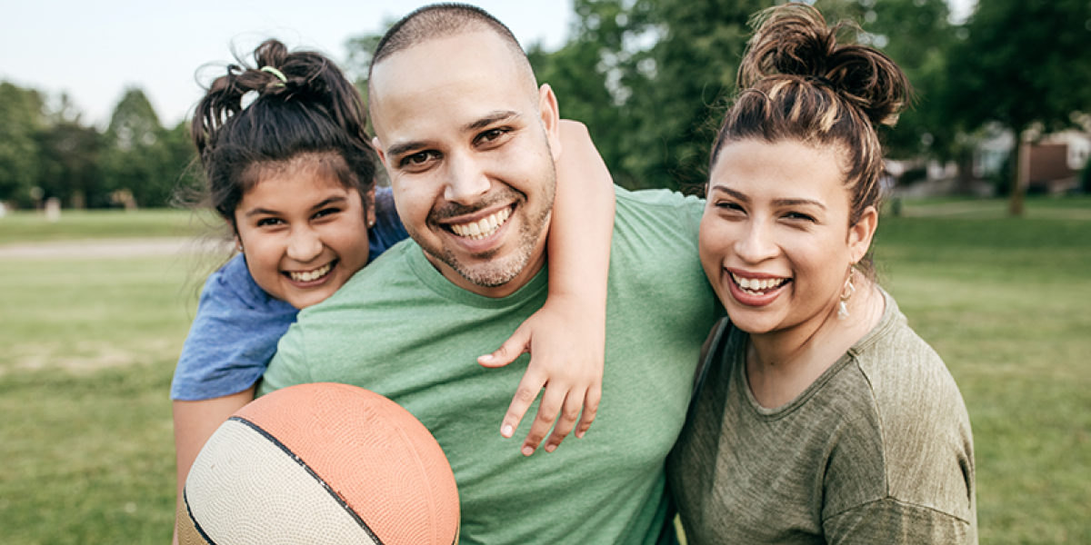 Mom, Dad and young daughter smiling at the camera, holding a basketball.