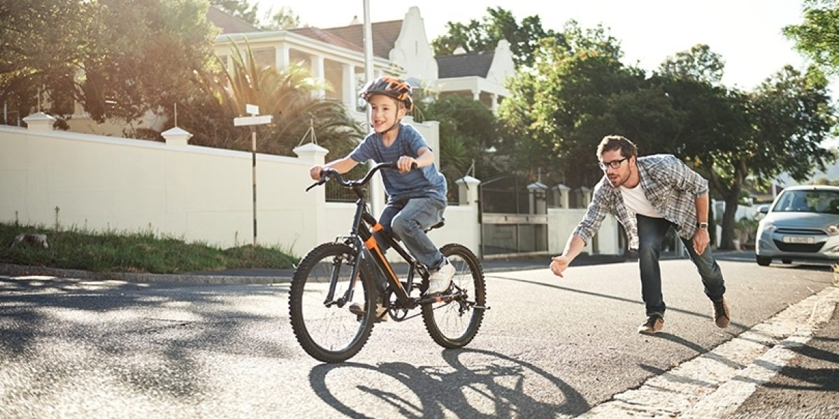 A man teaching a child to ride a bike on a suburban street.