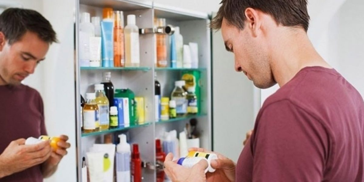 Man standing at his medicine cabinet looking at the labels of the medicine bottles.