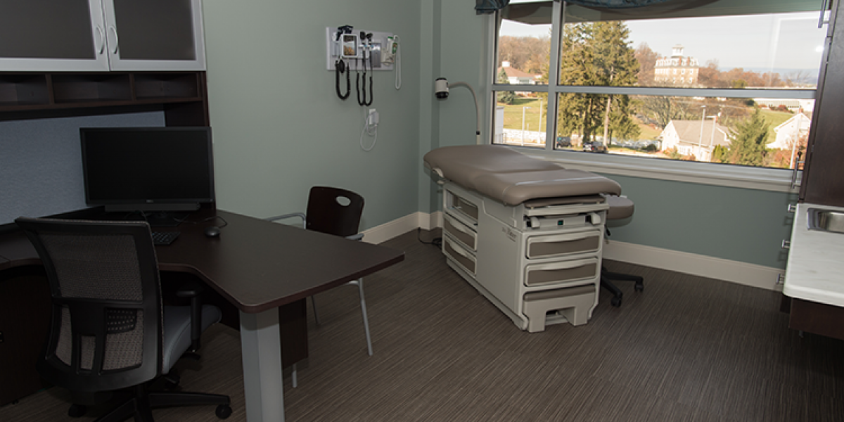 A medical examination room with that has a large black desk inside.