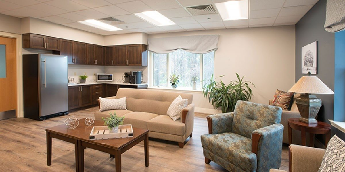 A room that has a refrigerator and cabinets on the left, and a seating area on the right.