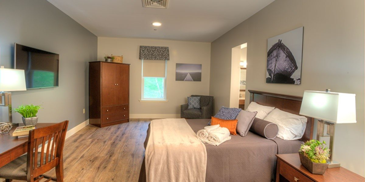 A bedroom with a bed on the right side of the room, and a desk, dresser, and mounted TV on the left side.
