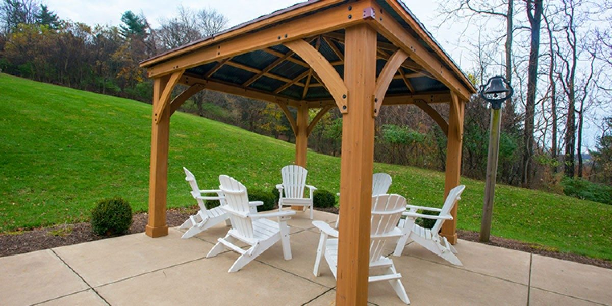 A pergola with multiple chairs underneath, beside a grassy field.