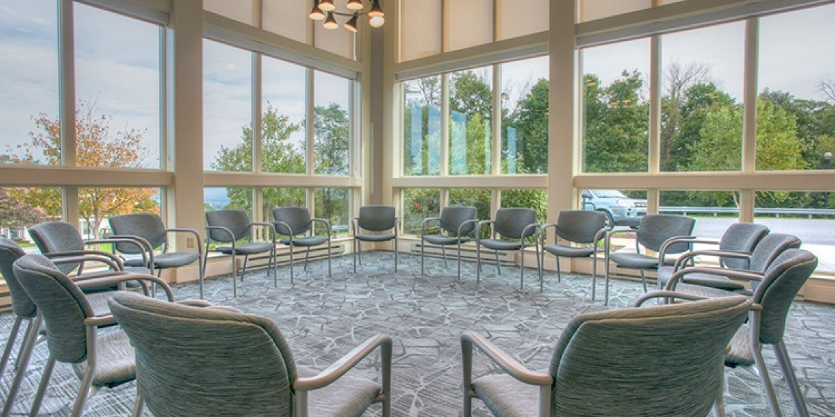 A room with floor to ceiling windows, and multiple chairs placed in a circle, facing in towards each other.