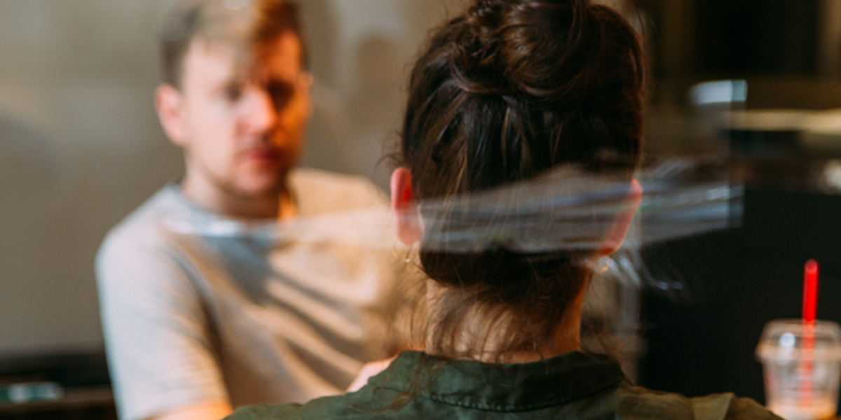 Soft focus through glass window on two people talking to each other in a coffee shop.