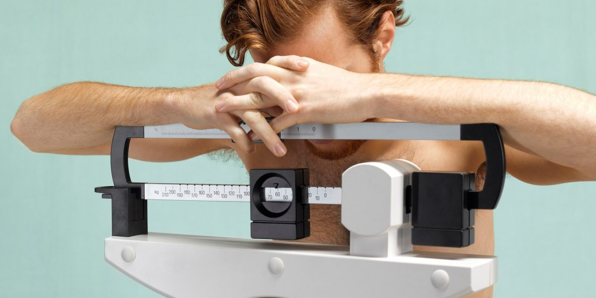 Man standing on a scale footing down at his feet with his arms over the top of the scale.