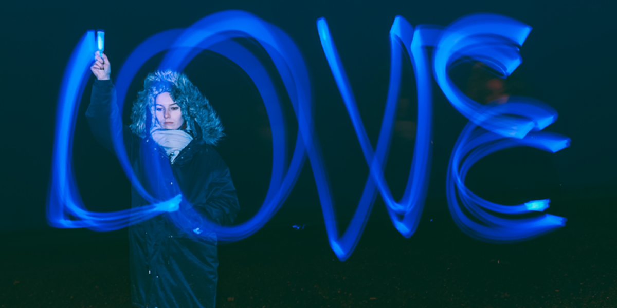 Woman in parka using a blue light to write out the word love in the dark.