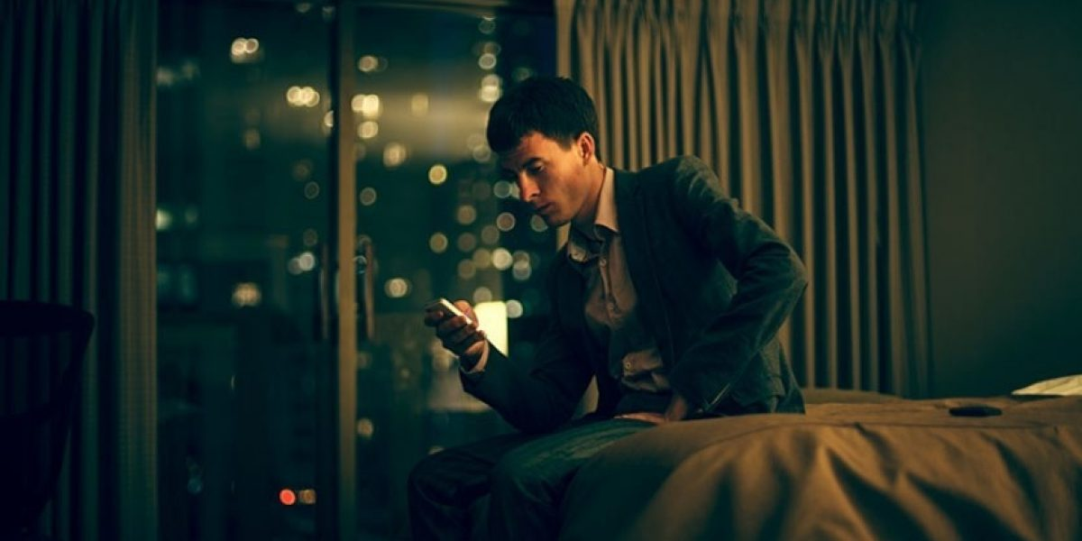 Person in a suit sitting on a hotel bed with a worried expression, looking at their phone.