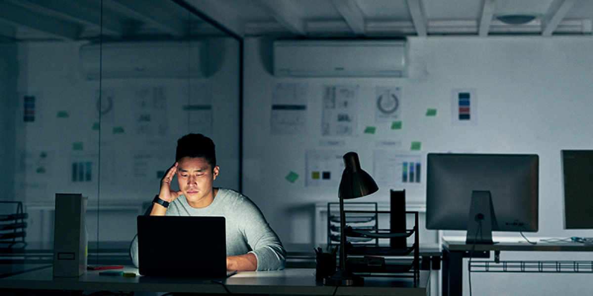 Man in a darkened and empty office, looking concerned and staring at a laptop screen.