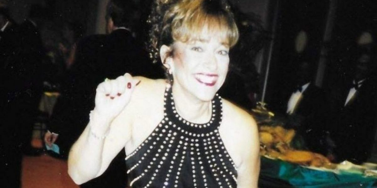 A woman in a black dress at a banquet dinner smiling and waving.