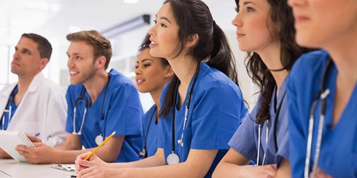 Group of young people in scrubs, sitting in class.