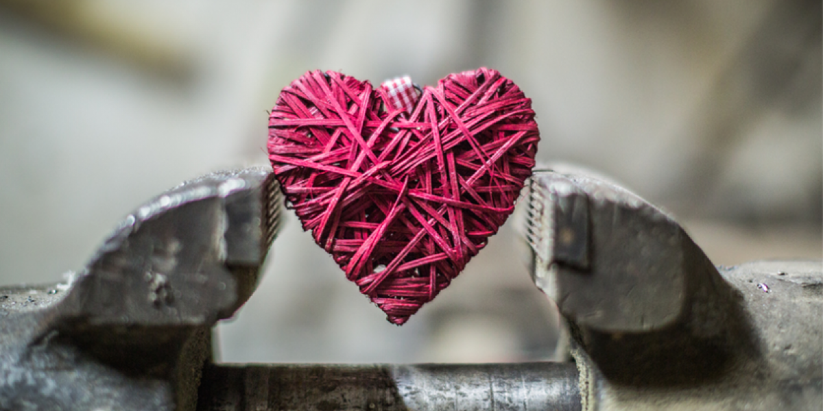 A pink heart made from wrapped twine, held within a vise.