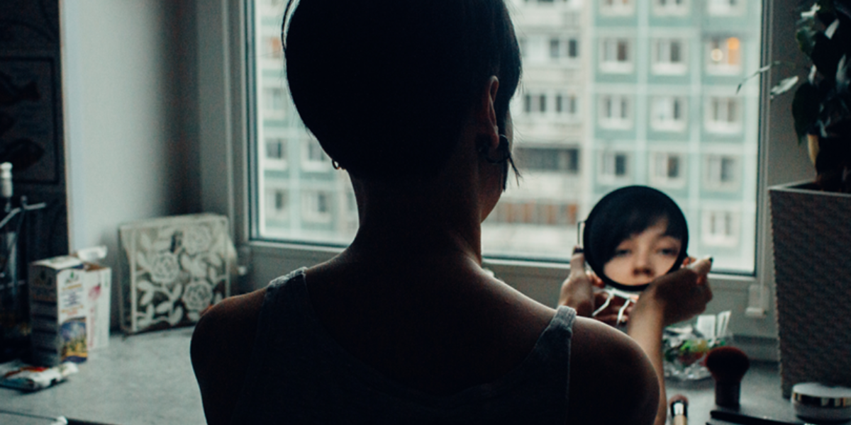 Person at a window, holding a small mirror to look at their reflection.