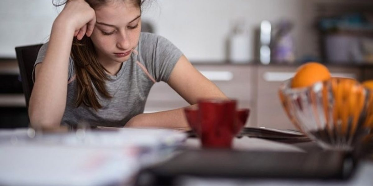 Teen sitting at the kitchen table looking down with her head in her hand.