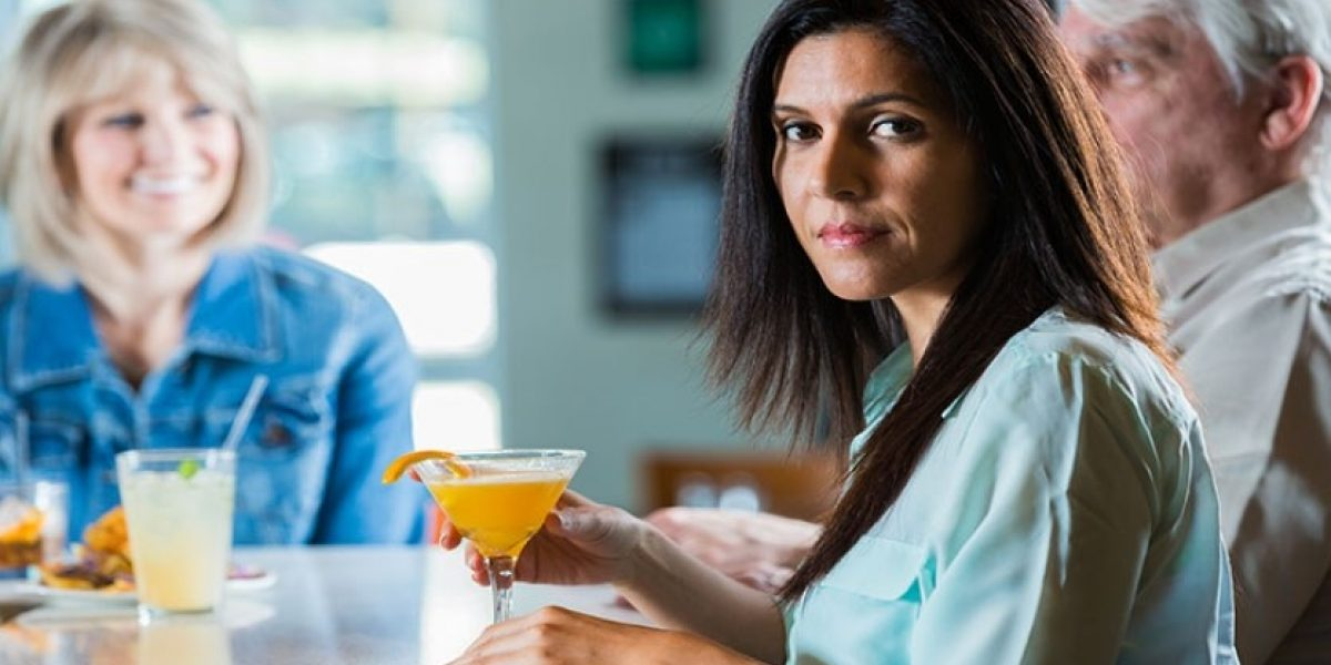 Woman sitting at a bar with her hand on a cocktail, looking at the camera.