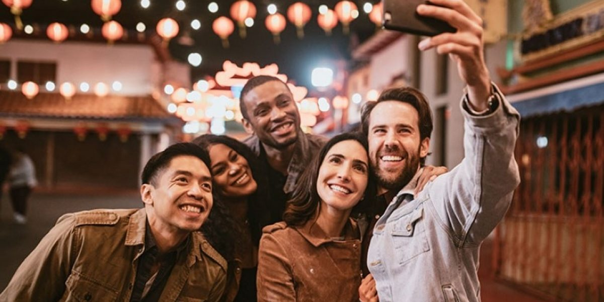 A group of friends taking a selfie outside at night time on the street.