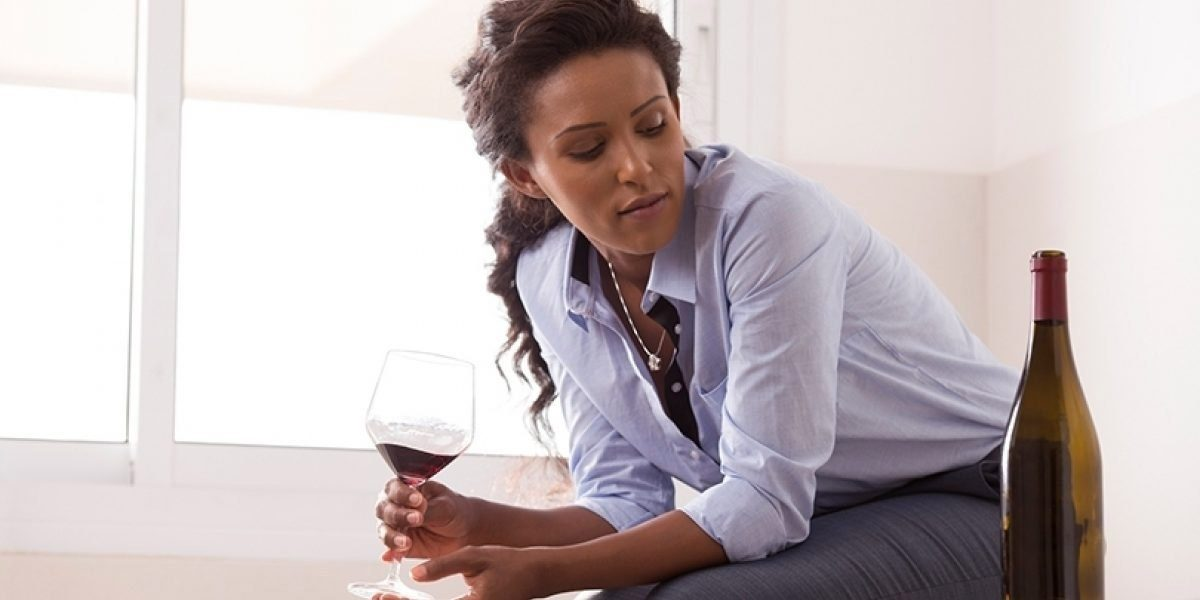 Woman holding a wine glass looking at the bottle.