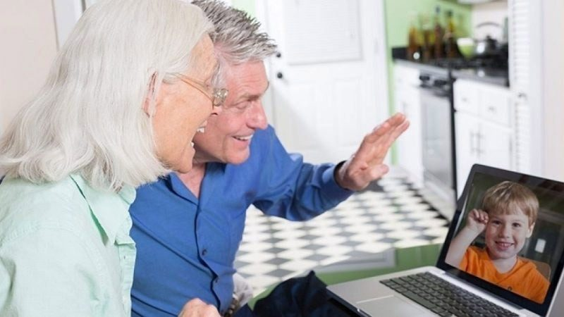 An older couple waving to their grandson on the computer screen.